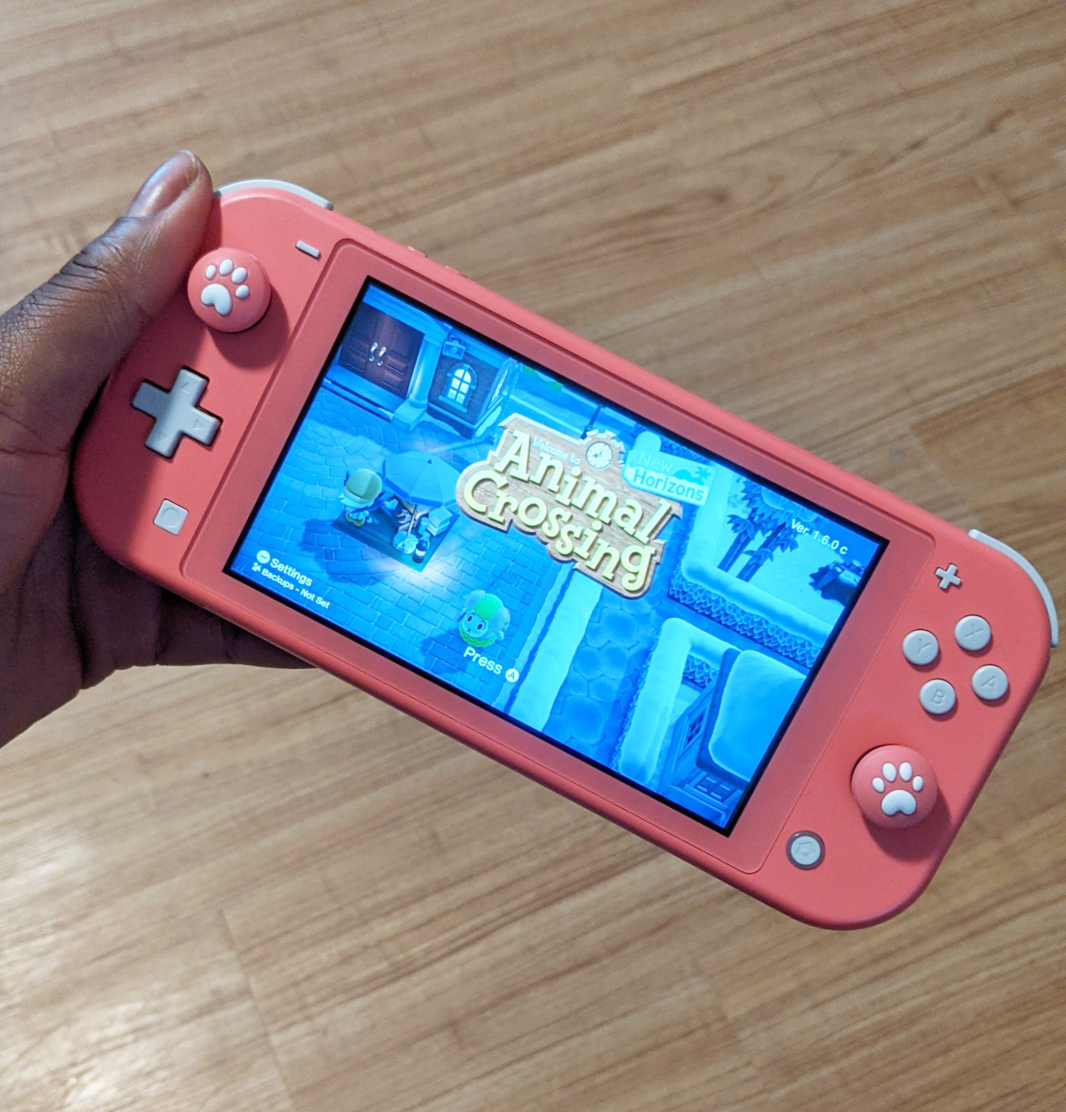 A person holding a Switch Lite console with silicone covers on the joysticks