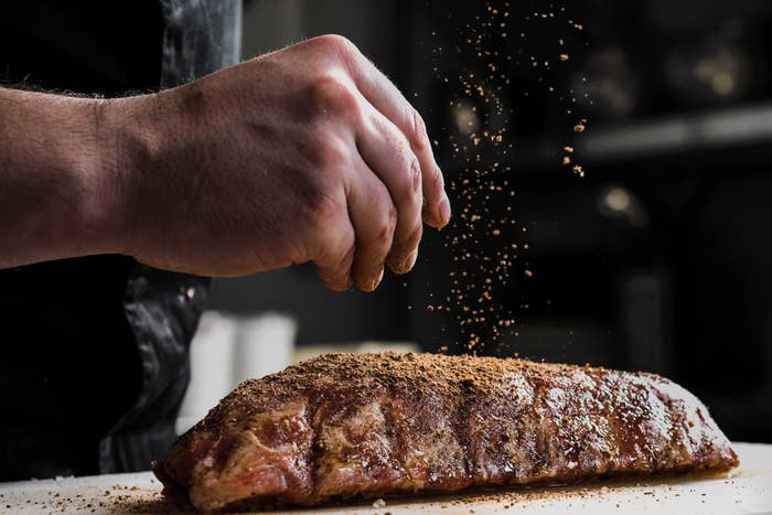 The hand of a male chef putting salt and spices on meat