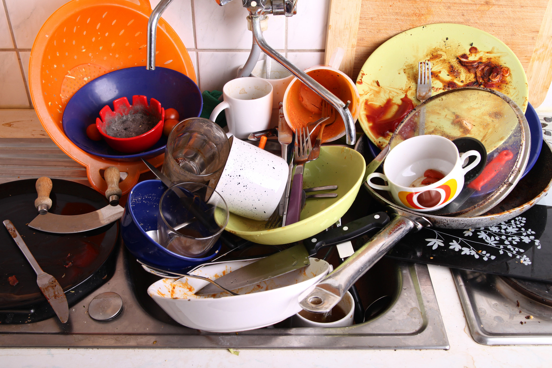 Huge pile of dirty pots, pans, cups, and dishes in the sink waiting to be washed