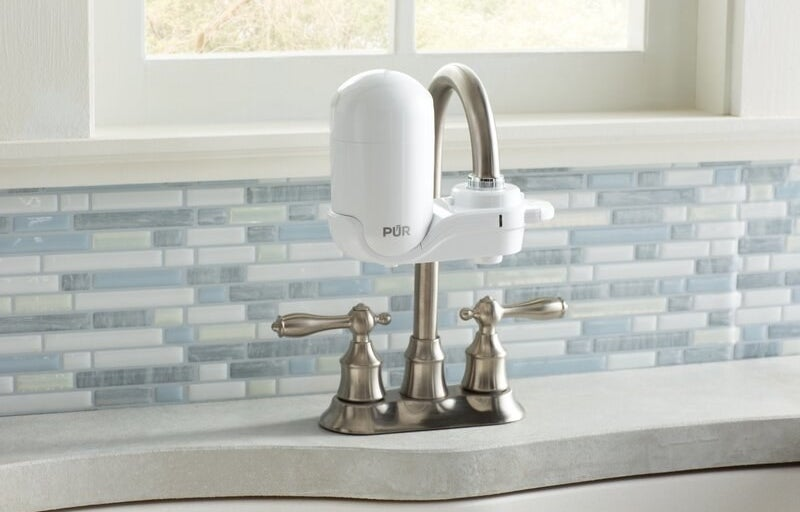 a white water filter attached to a faucet in a kitchen