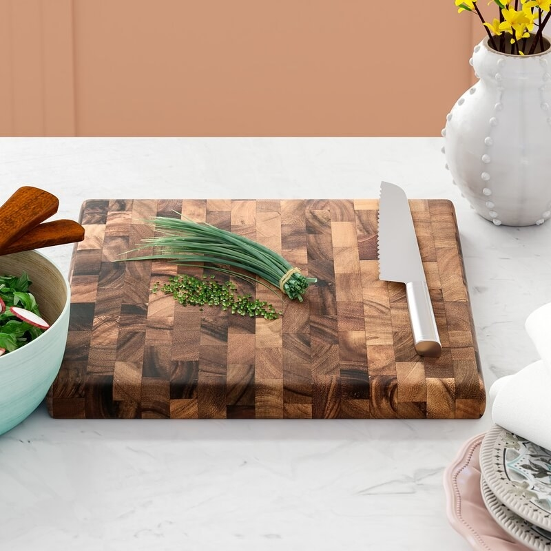 a brown wooden cutting board with chives and a knife on top of it