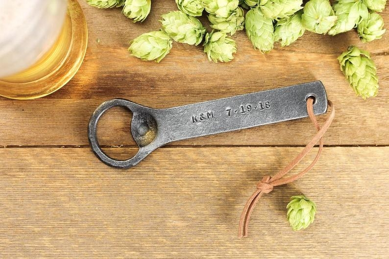 An iron bottle opener with K&M 7-19-18 etched onto it