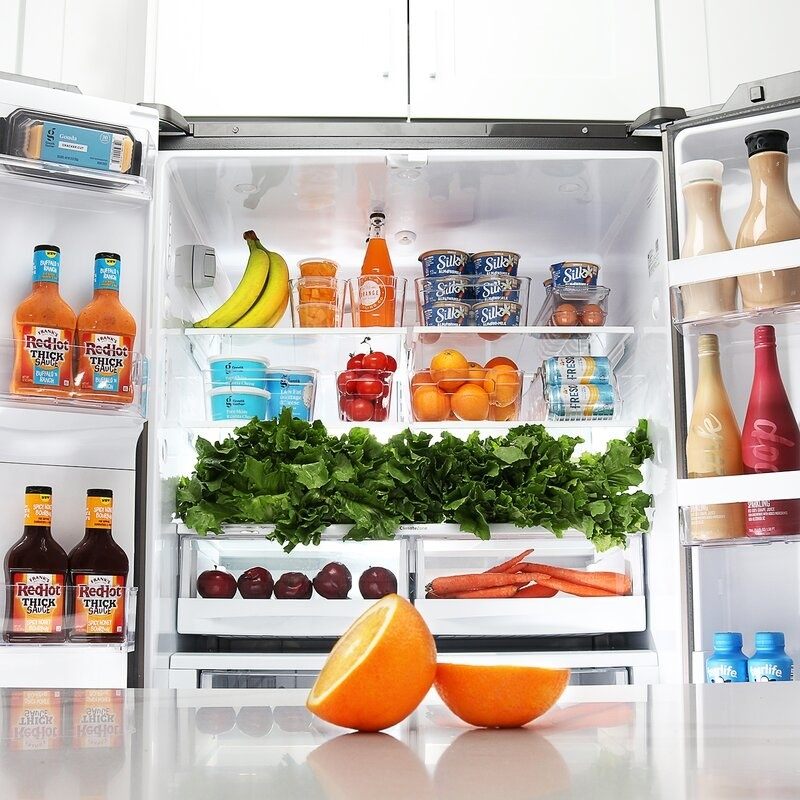 an open fridge with clear food bins on its shelves holding produce and yogurt