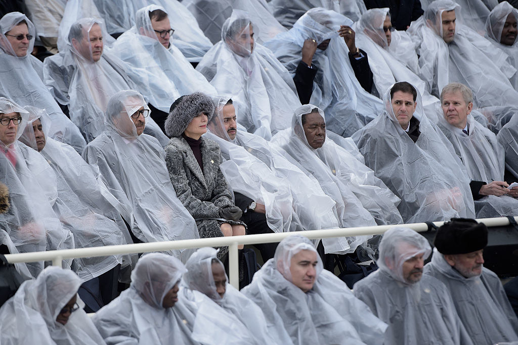 Guests wearing plastic rain ponchos with one woman wearing a fur hat and matching coat