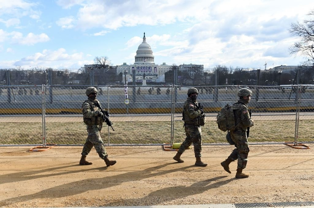 National Guardsmen patrolling the Capitol perimeter with weapons