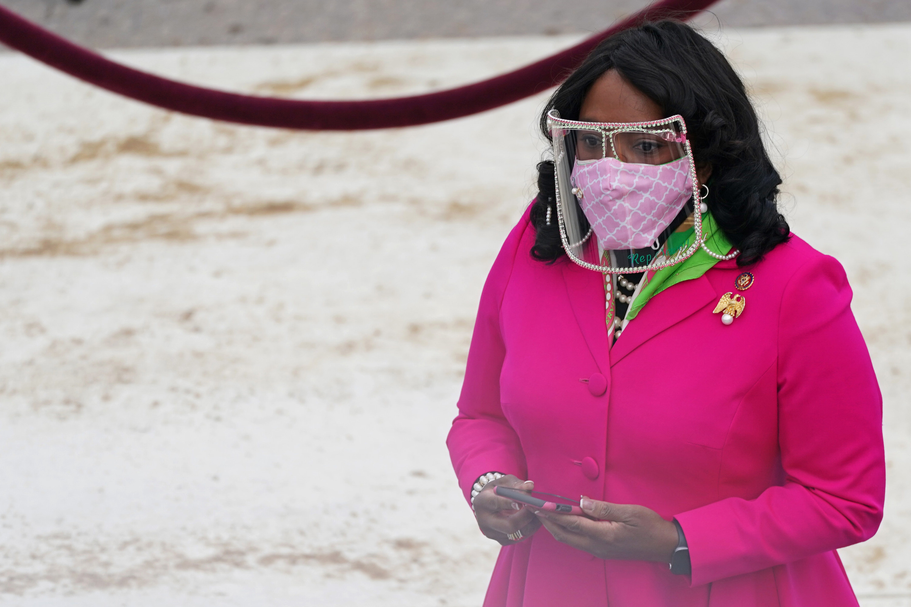 Rep. Terri Sewell in a pink coat, pearl-studded face shield and pink face mask at the inauguration.