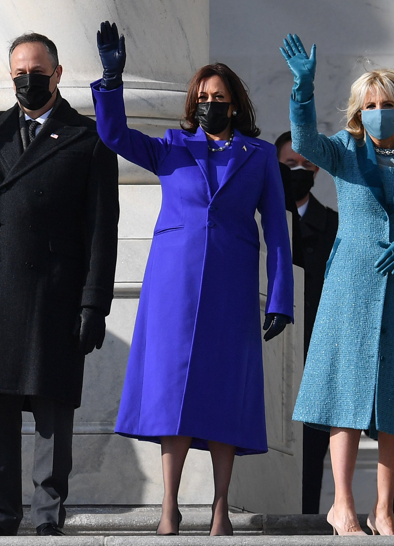 Kamala Harris is a long, deep blue coat with matching shirt, dark blue leather gloves, and black facemask.
