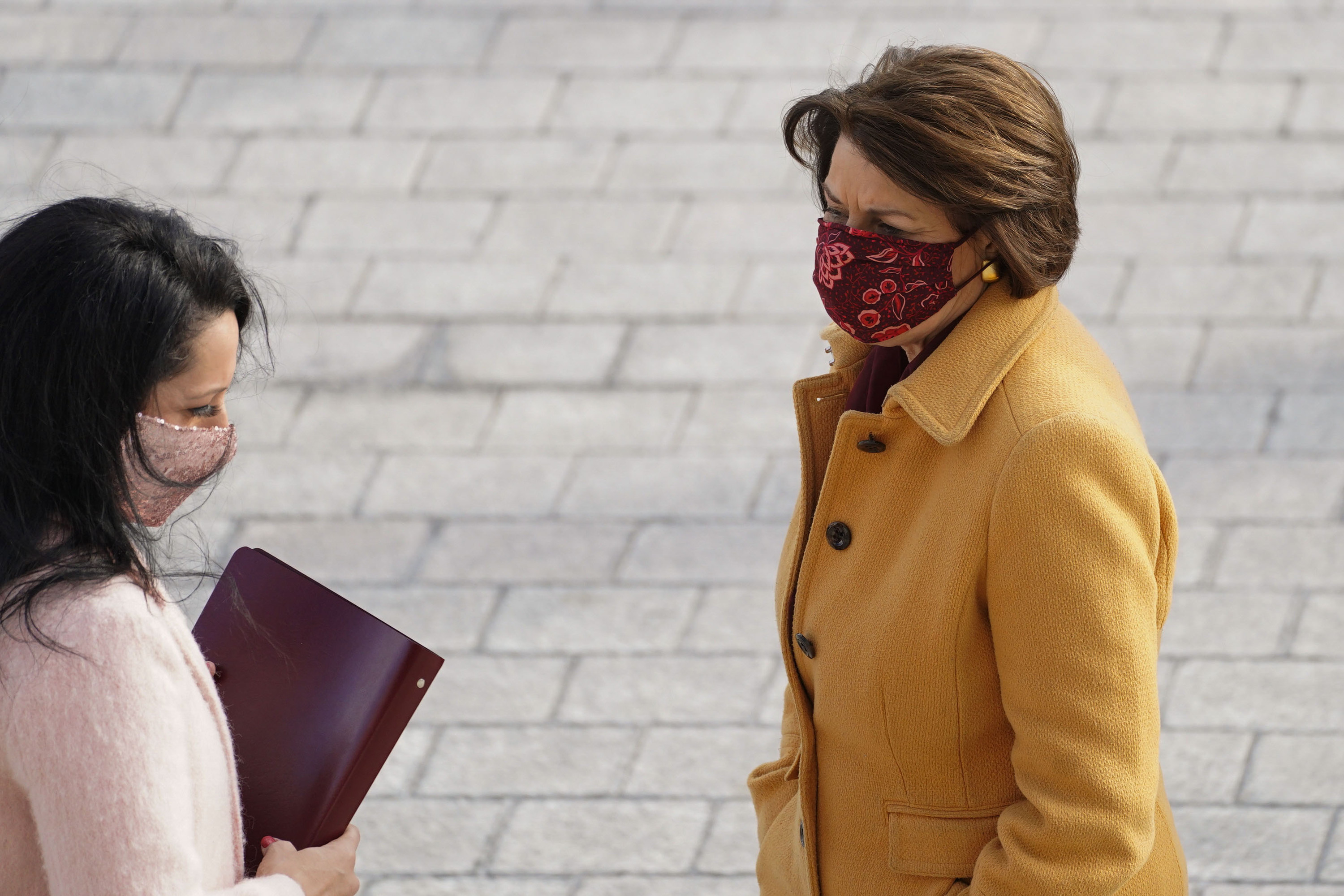 Sen. Amy Klobuchar in a yellow coat and red floral face mask at the inauguration, standing next to a woman in a pink coat and pink face mask.