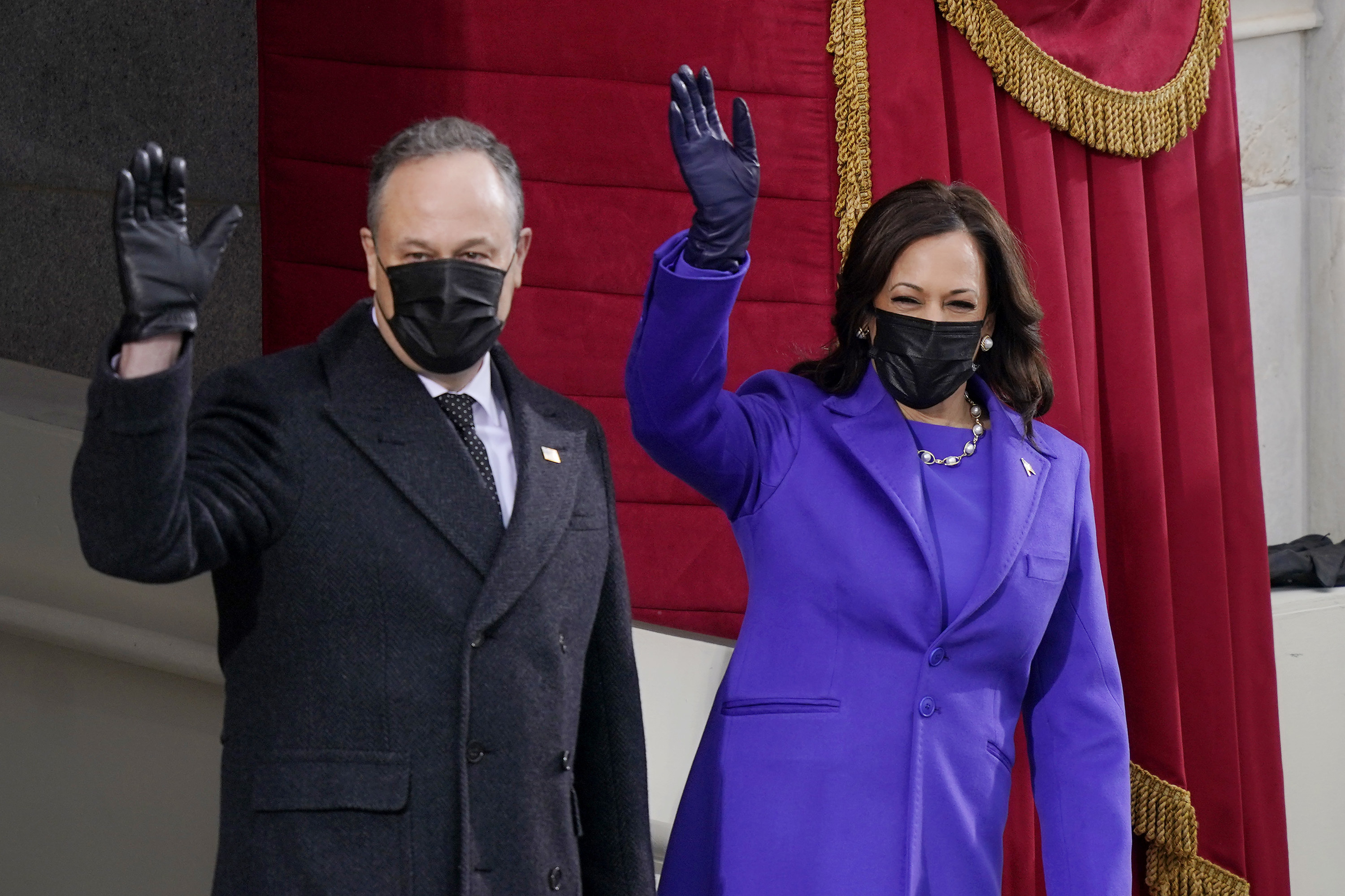Vice President Kamala Harris in a purple suit and black face mask and her husband Doug Emhoff in a black face mask, standing and waving at the inauguration.