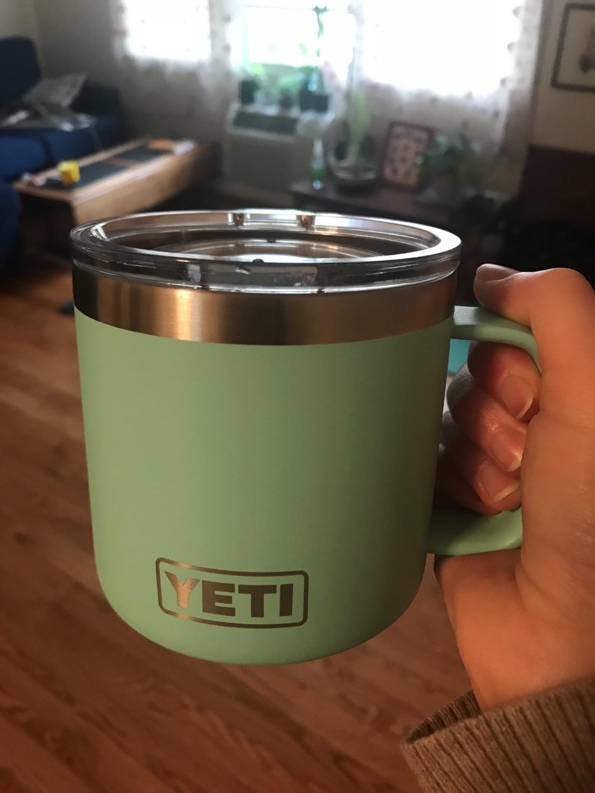 Reviewer holding seafoam Yeti mug
