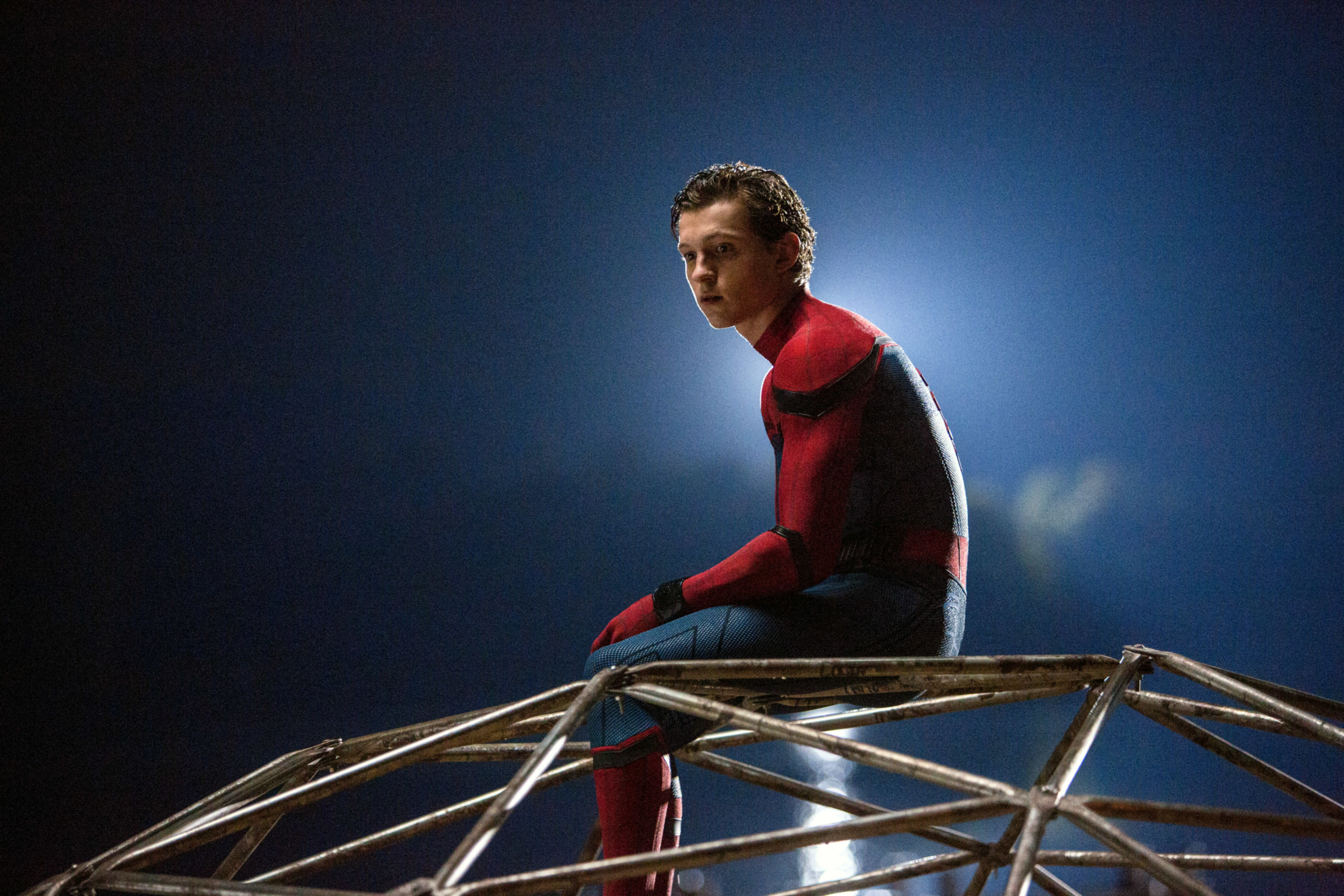 Spider-Man sitting unmasked on top of jungle gym geo dome