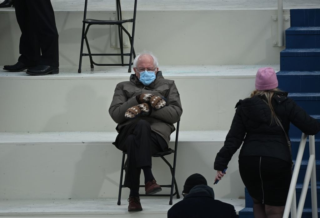 Bernie Sanders sitting cross-legged and six feet away from other guests with his face mask and gloves on
