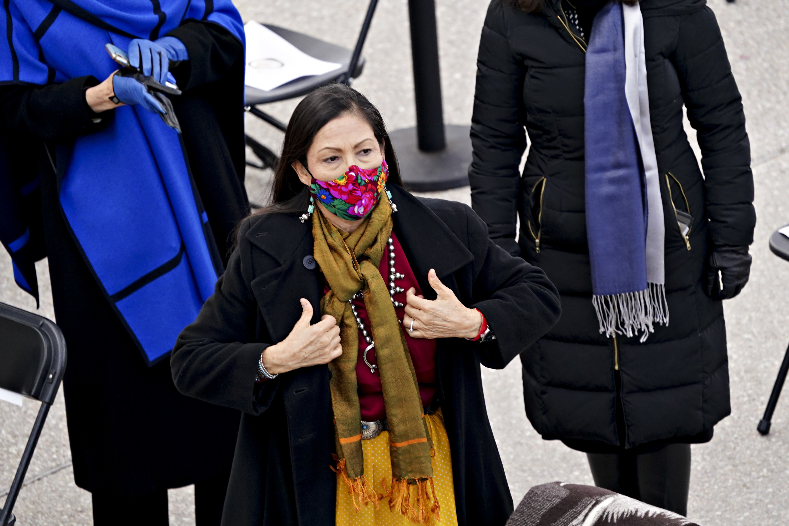 Representative Deb Haaland standing, in a floral face mask and yellow scarf, at the inauguration.