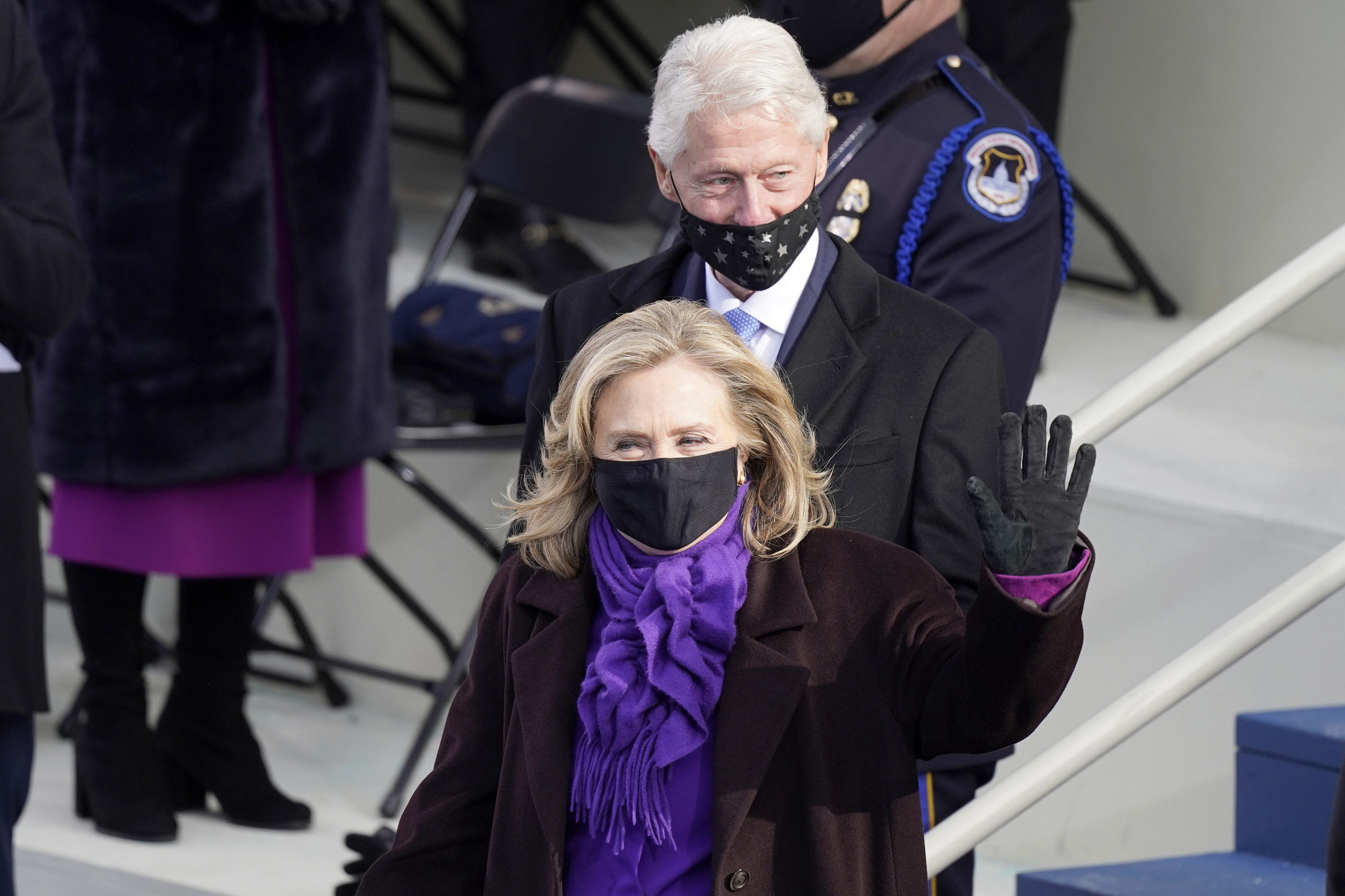 Bill Clinton with a star mask on only his chin and mouth and Hillary Clinton in a black face mask at the inauguration.
