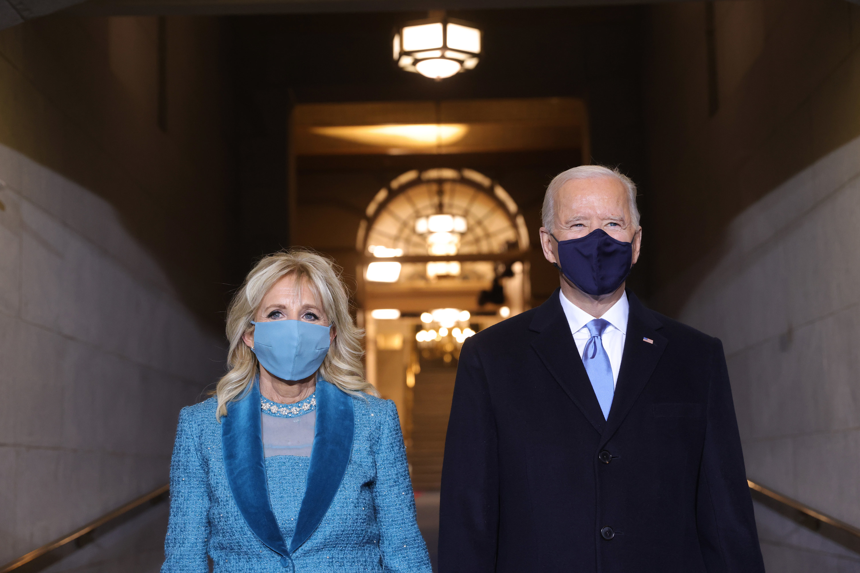 U.S. President Joe Biden with a face mask and Jill Biden with a blue face mask standing on the West Front of the U.S. Capitol on January 20, 2021 in Washington, DC. during today's inauguration ceremony.