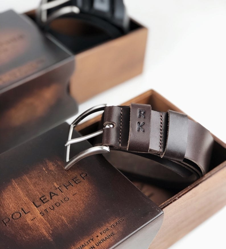 A personalized leather belt in a wooden box