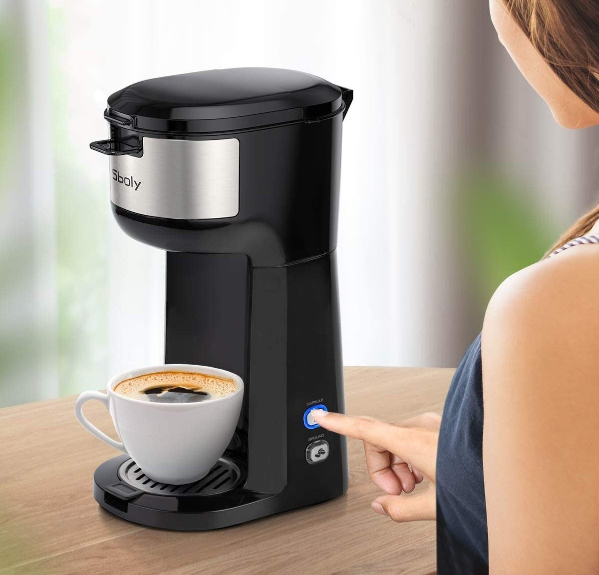 Model pressing button on the side of single serve coffee maker