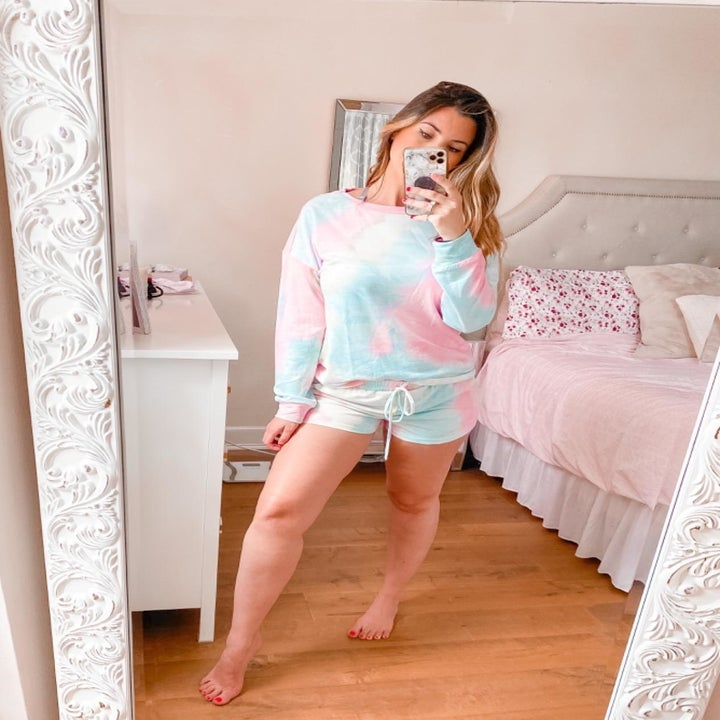 reviewer wearing the long-sleeve and short set in pink, yellow, and blue tie-dye