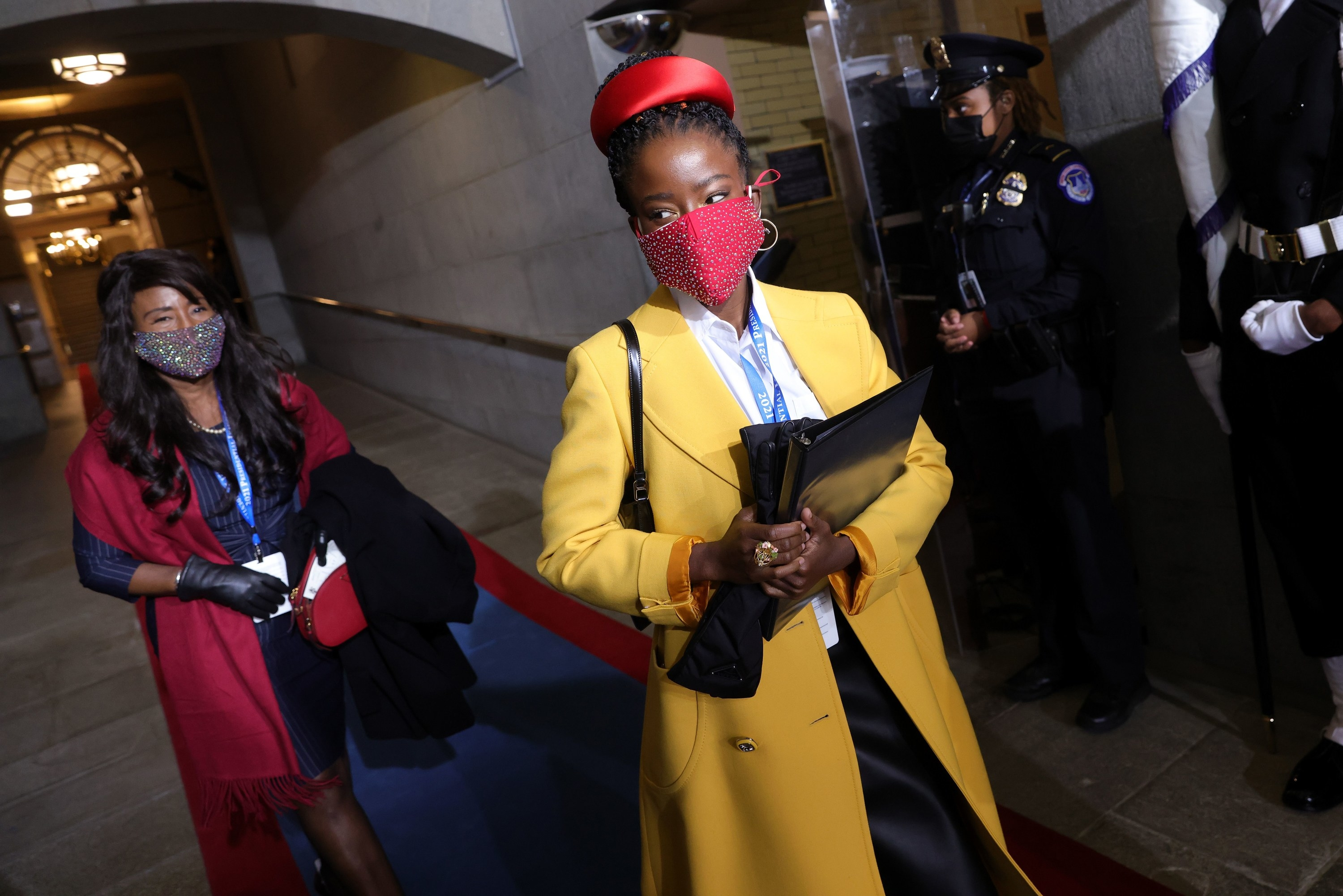 National youth poet laureate Amanda Gorman in a yellow coat and red studded face mask arriving at the inauguration, with another woman behind her in a red coat and floral face mask.