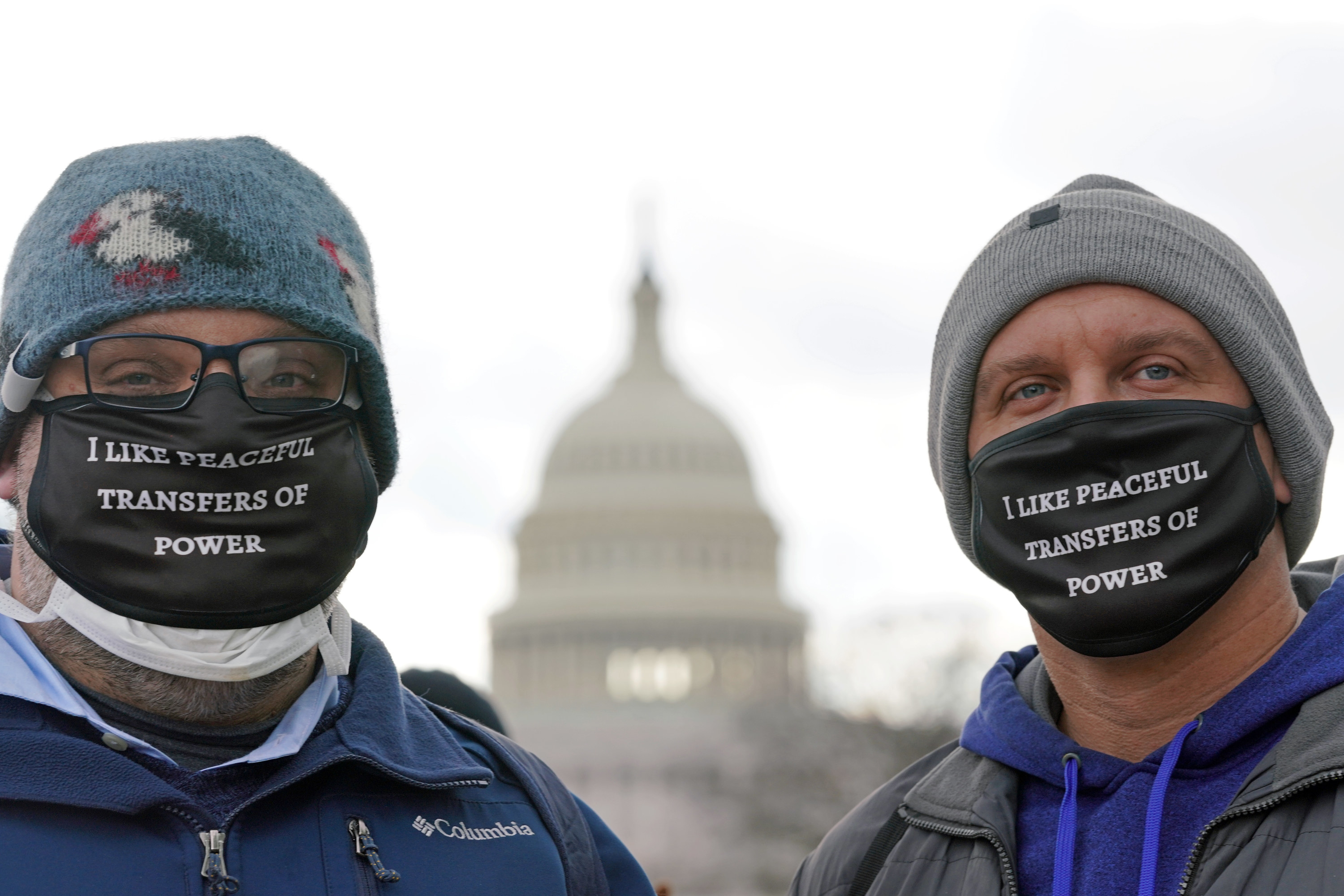 """People wearing masks reading """"I like peaceful transfers of power"""" pose in front of the U.S. Capitol before the start of the inauguration of U.S. President-elect Joe Biden."""