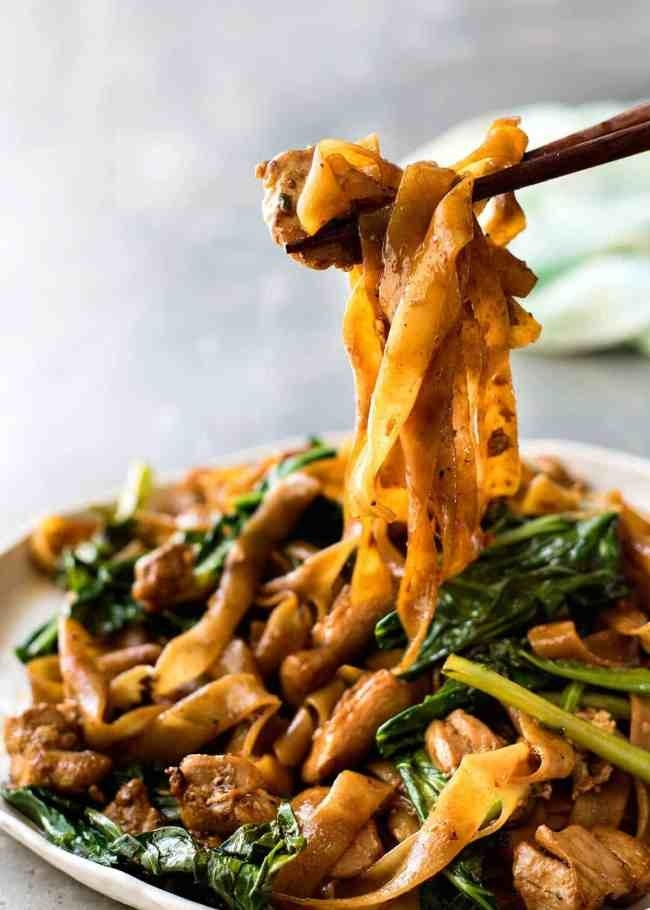 A plate of saucy pad see ew noodles with Chinese broccoli.