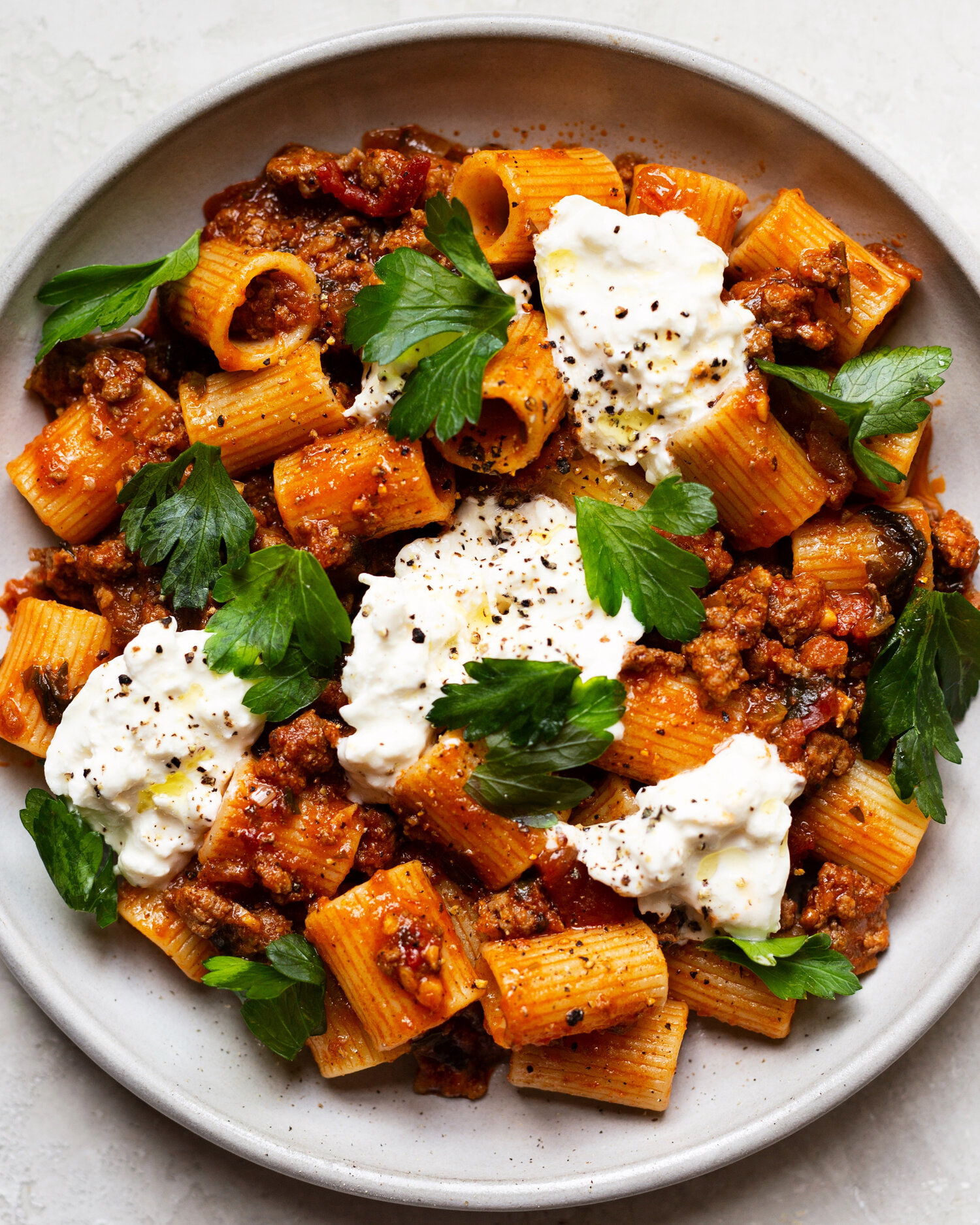 A big plate of rigatoni with burrata, meat sauce, and herbs.