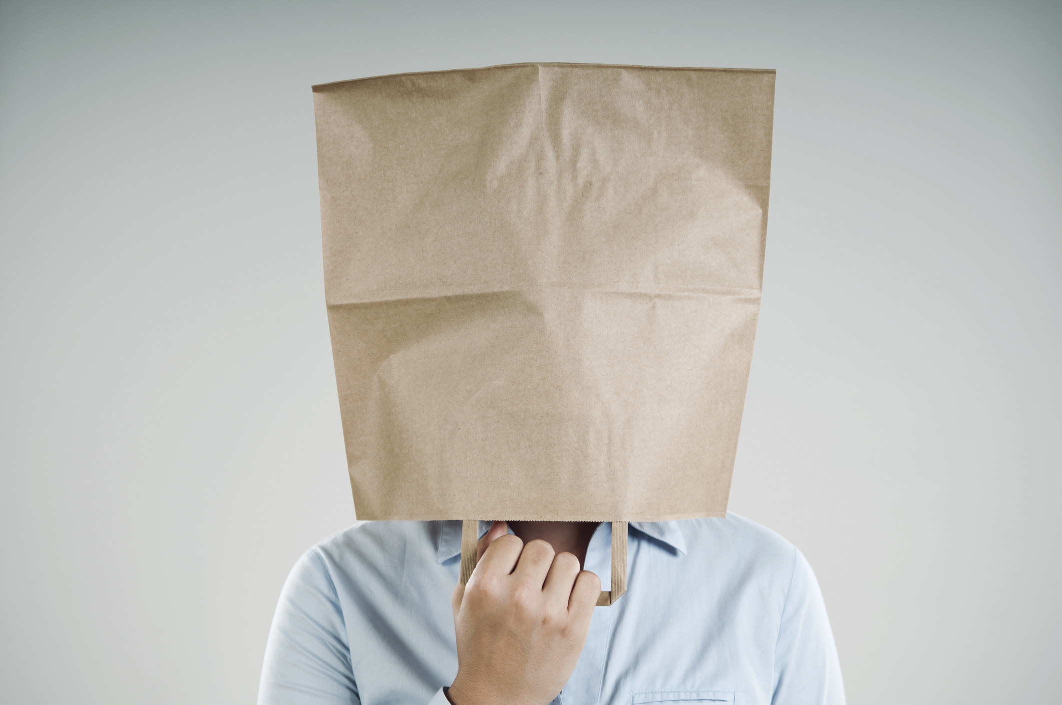 Someone wears a paper bag over their head