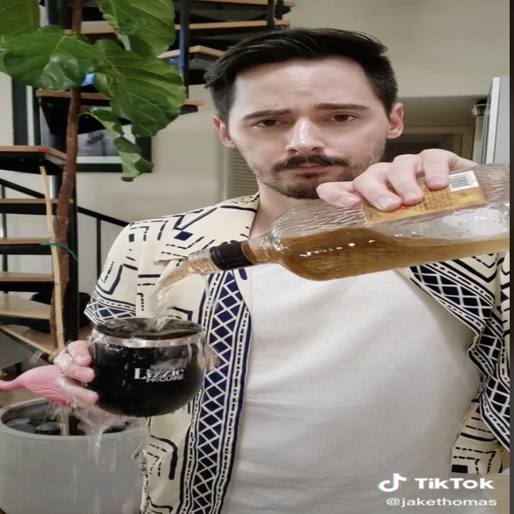 Jake Thomas pouring alcohol into a lizzie mcguire mug