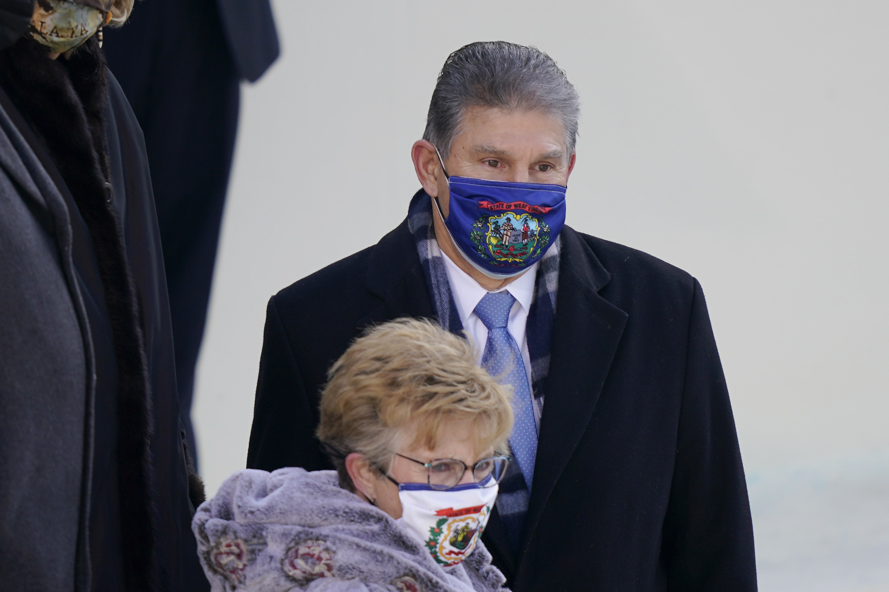 Sen. Joe Manchin and a woman wearing face masks with the state of West Virginia flag at the inauguration.
