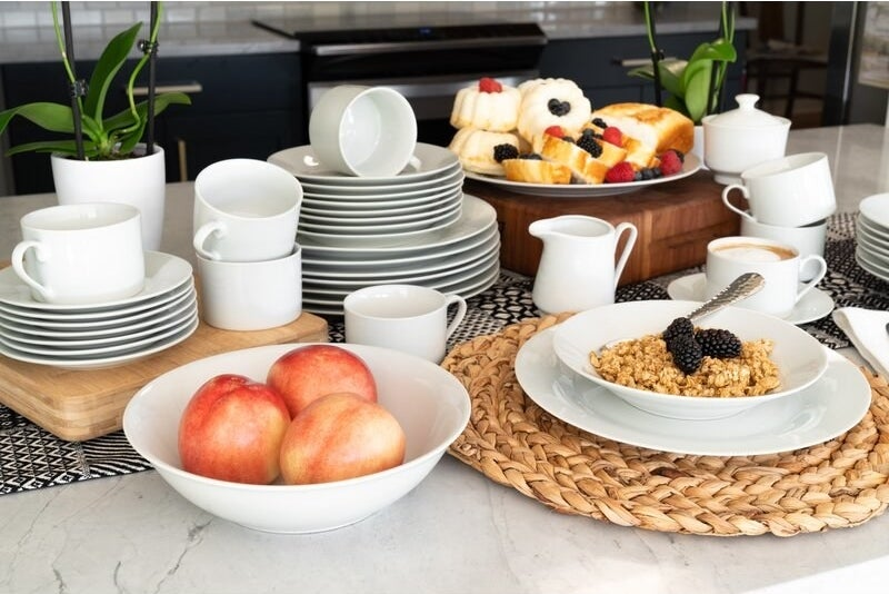 a white circular dinnerware set that is holding food on a counter
