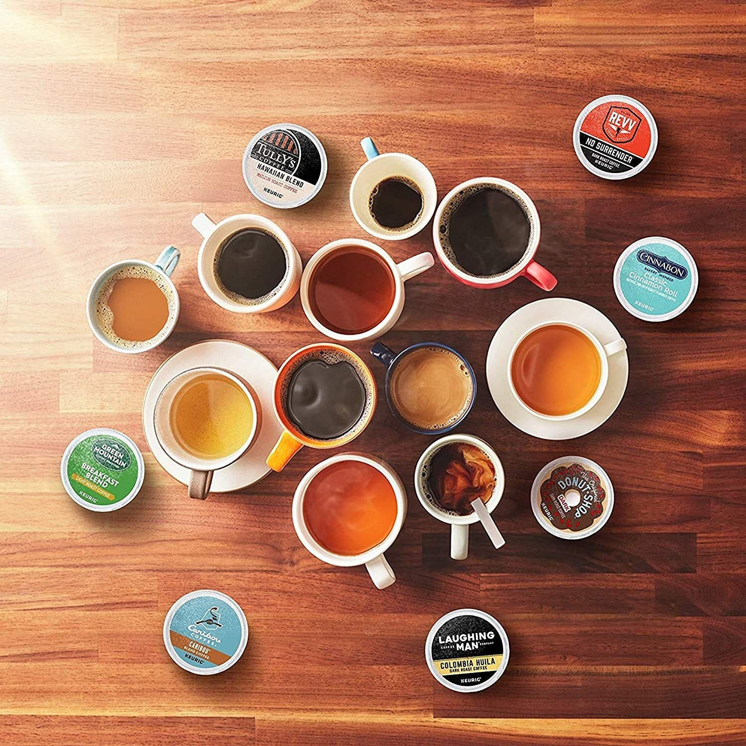 Coffee cups on table surrounded by various k-cups