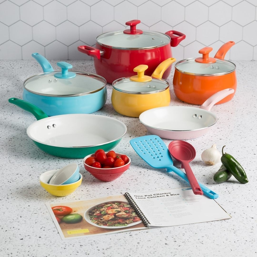A bunch of pots and pans on a counter with a recipe book and pinch bowls