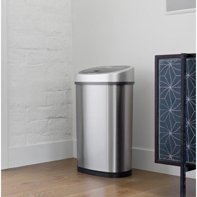 a silver motion sensor trash bin standing in a corner