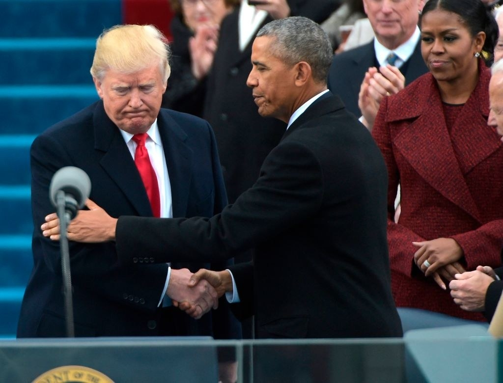 Former President Obama shaking hands with former President Trump on stage