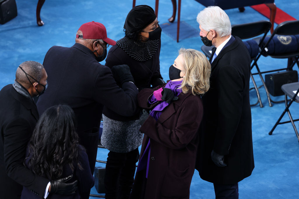 Former President Bill Clinton and Secretary Hilary Clinton greeting other guests with arm bumps