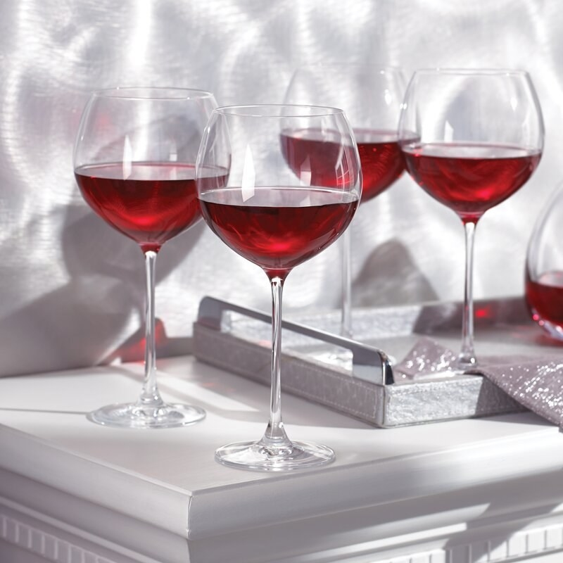 a set of four thin stemmed red wine glasses