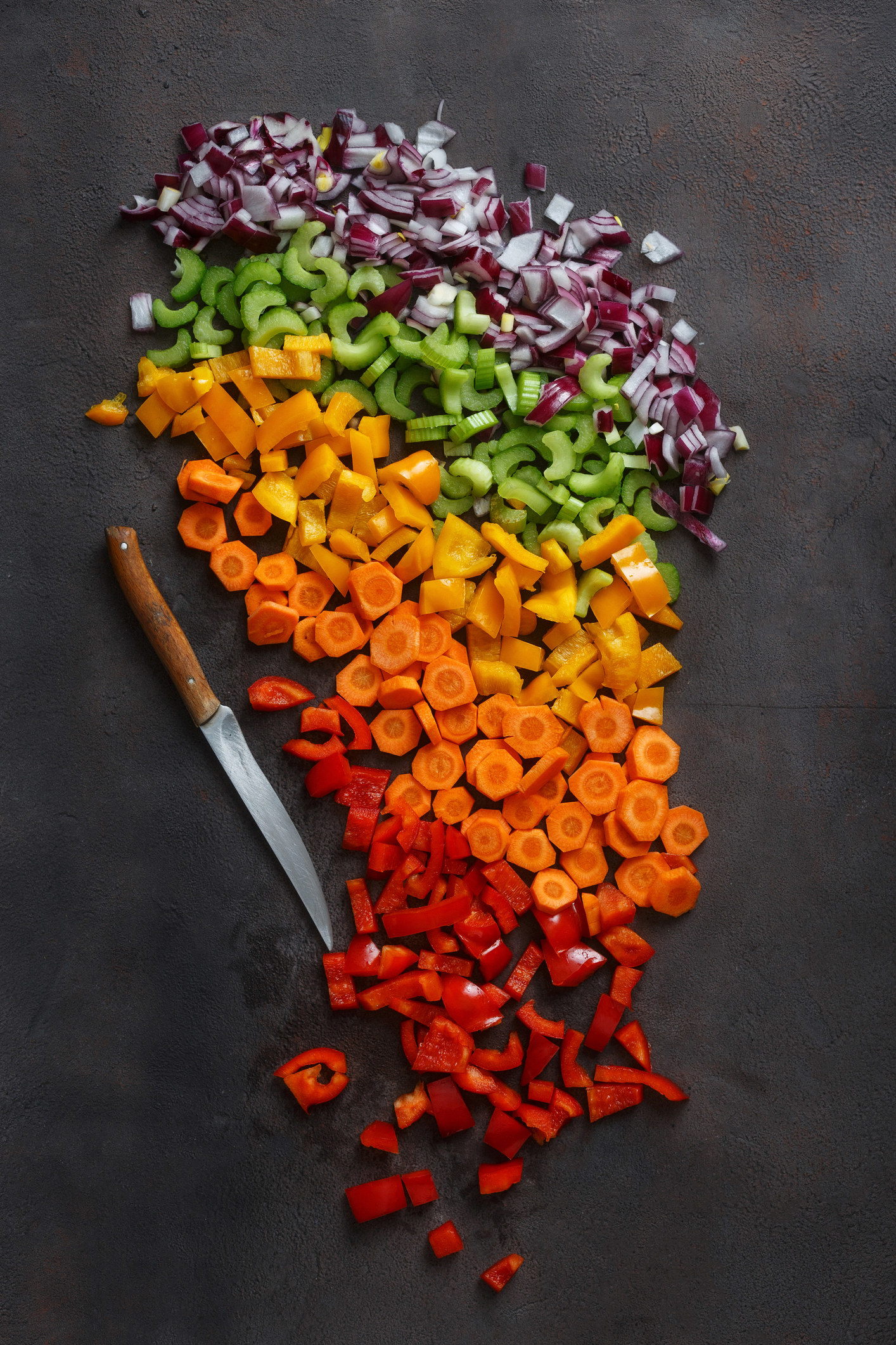 Evenly cut carrots, peppers, onions, and cucumbers
