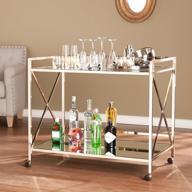 a gold bar cart with two shelves holding alcohol and wine glasses