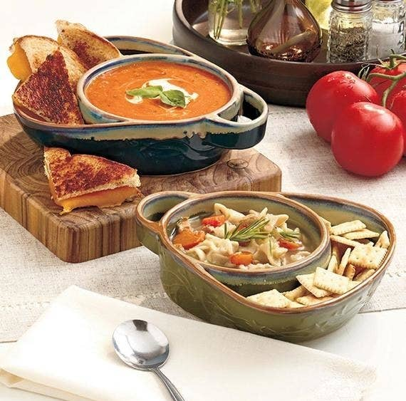 A pair of bowls with attached handles and trays filled with soup and crackers in one and soup and toasted cheese in the other