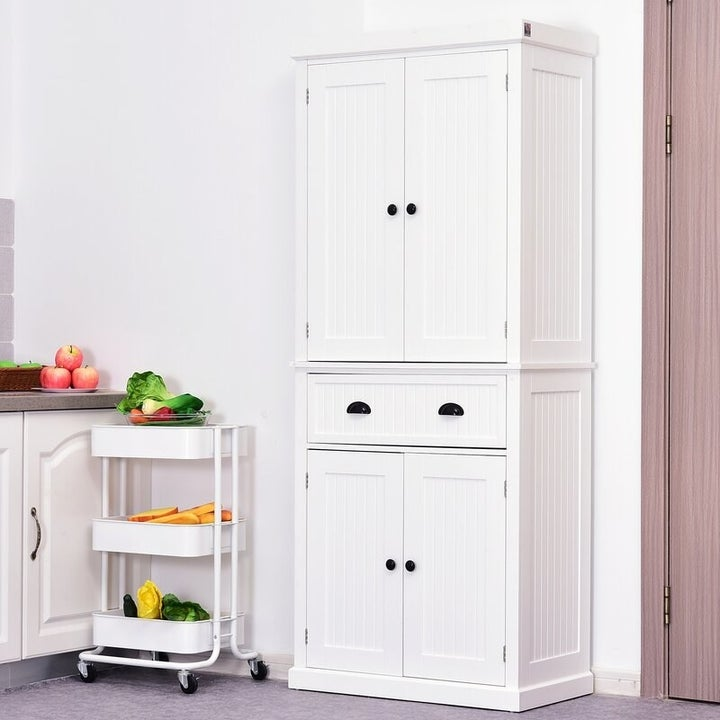 a closed white kitchen pantry with four doors and two drawers