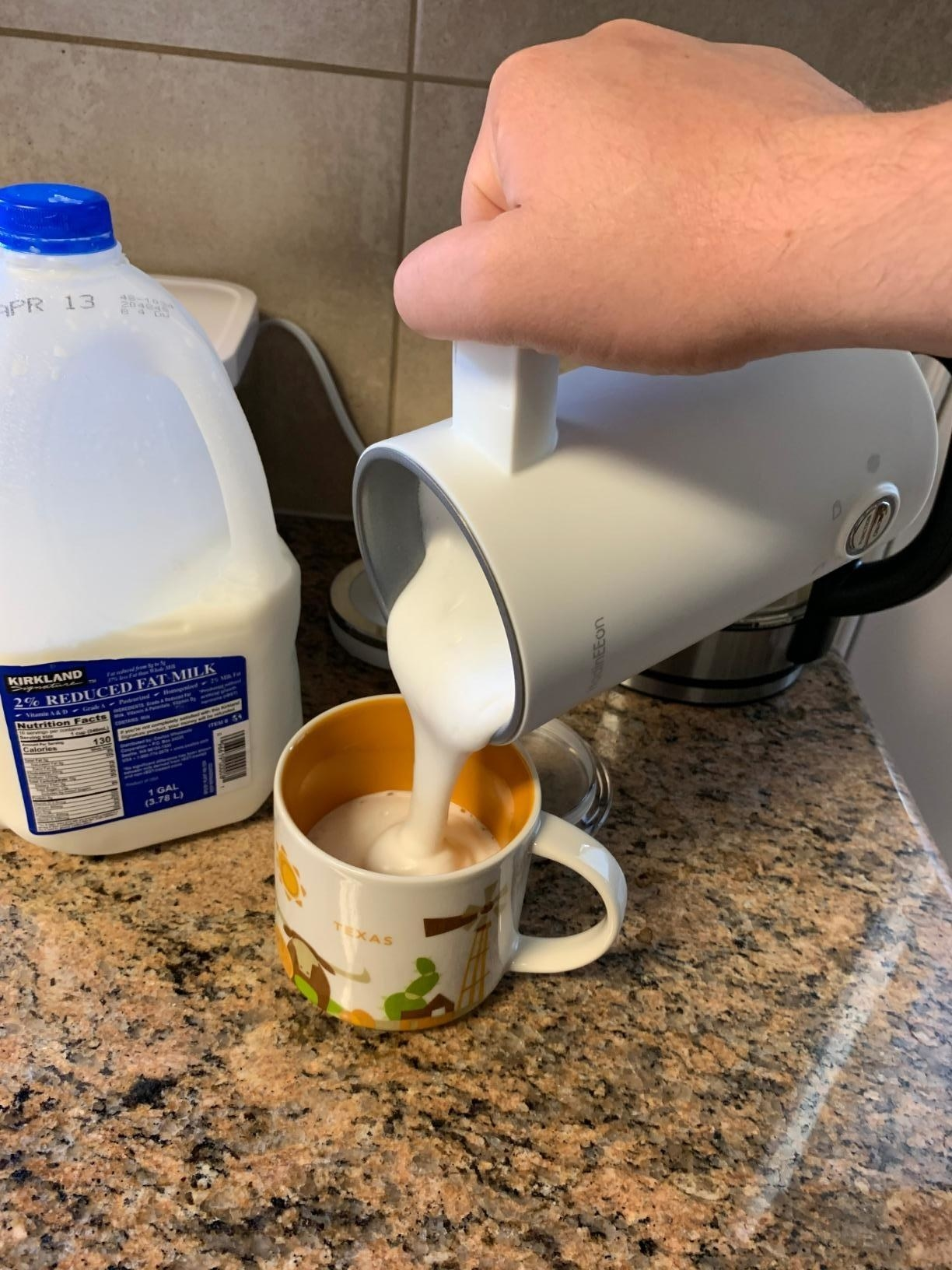 Reviewer pouring frothed milk from milk frother into coffee cup