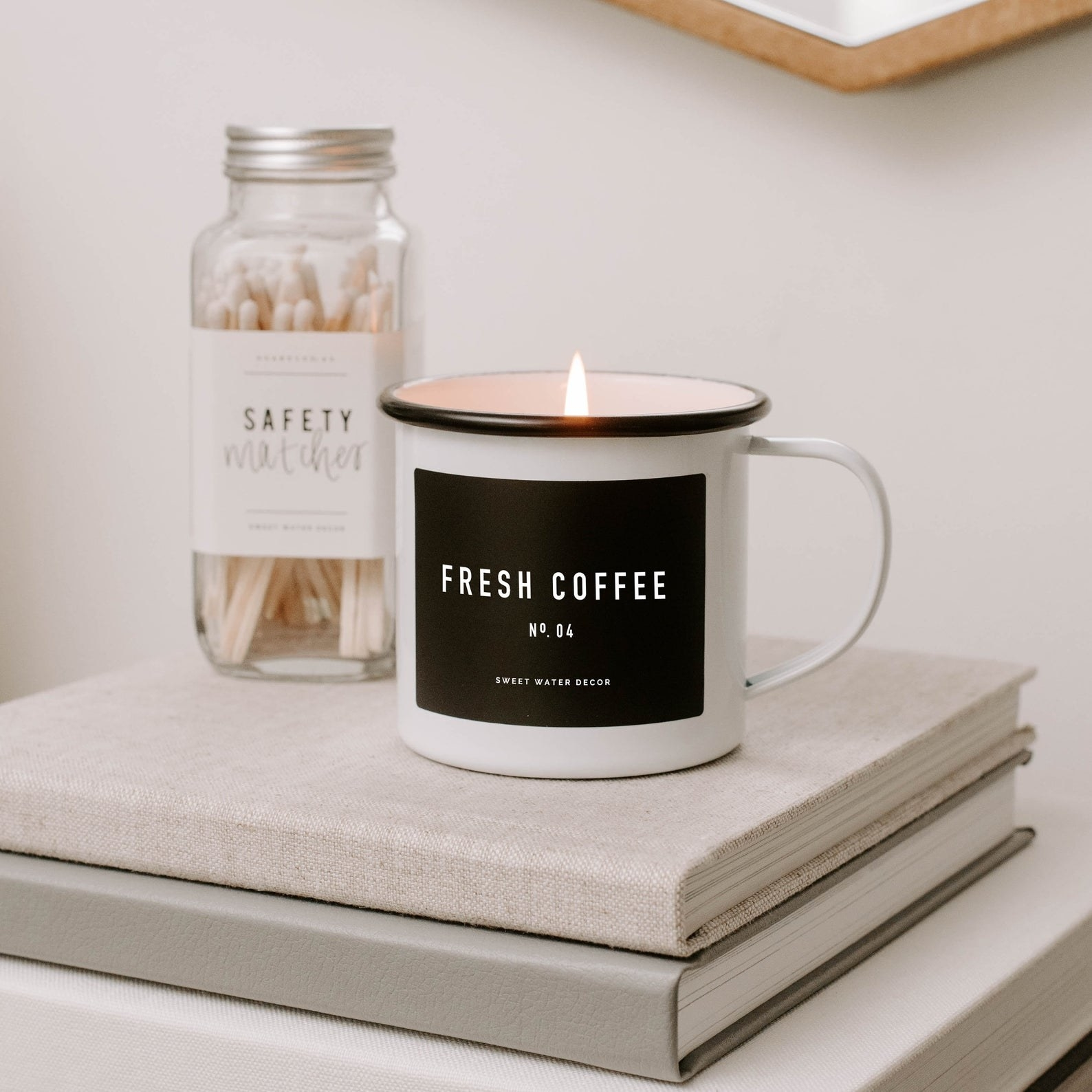 Fresh Coffee candle placed on stack of books