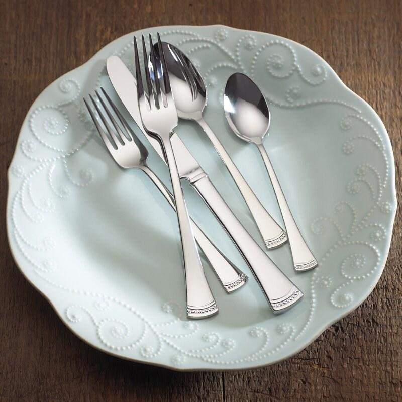 a tablespoon, dinner fork, dinner knife, salad fork, and teaspoon resting on a plate