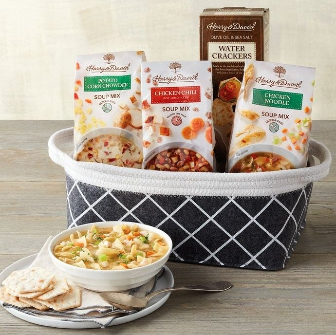 A basket filled with three soup mixes and a box of crackers