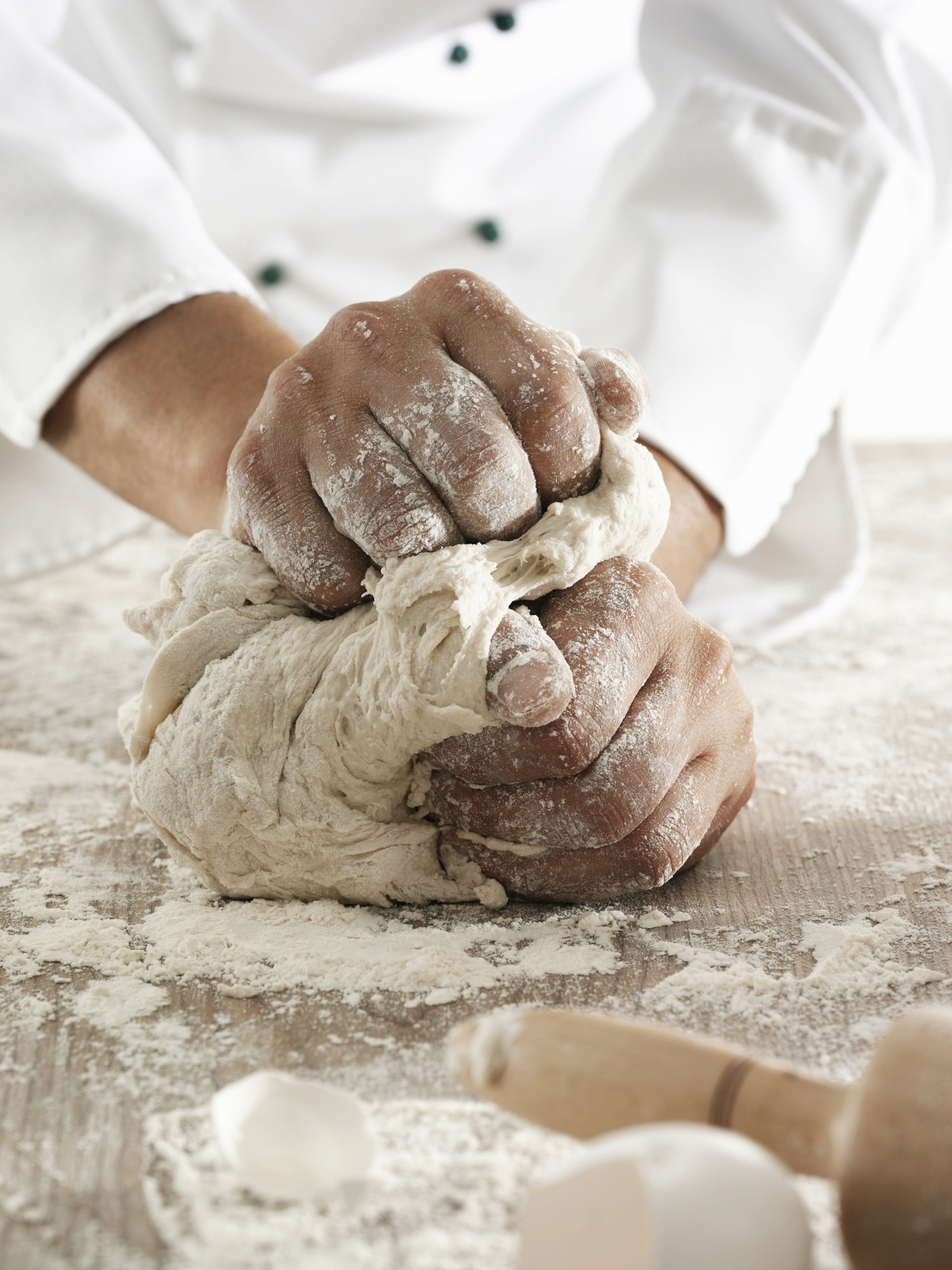 Male chef kneading dough