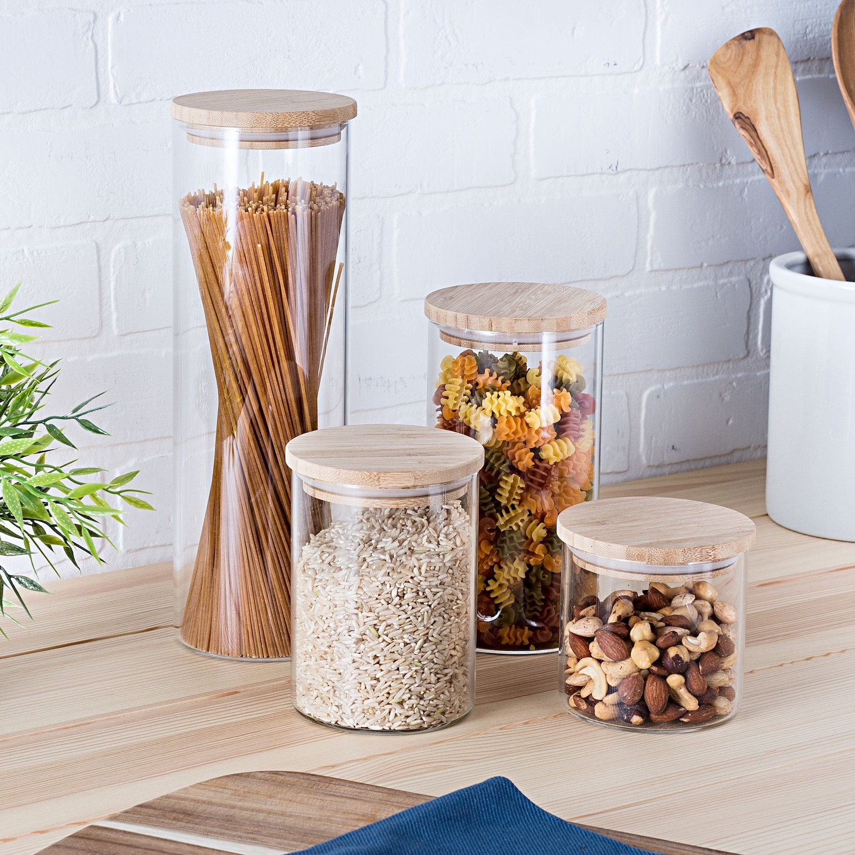 The four storage jars filled with different dried goods on a kitchen counter