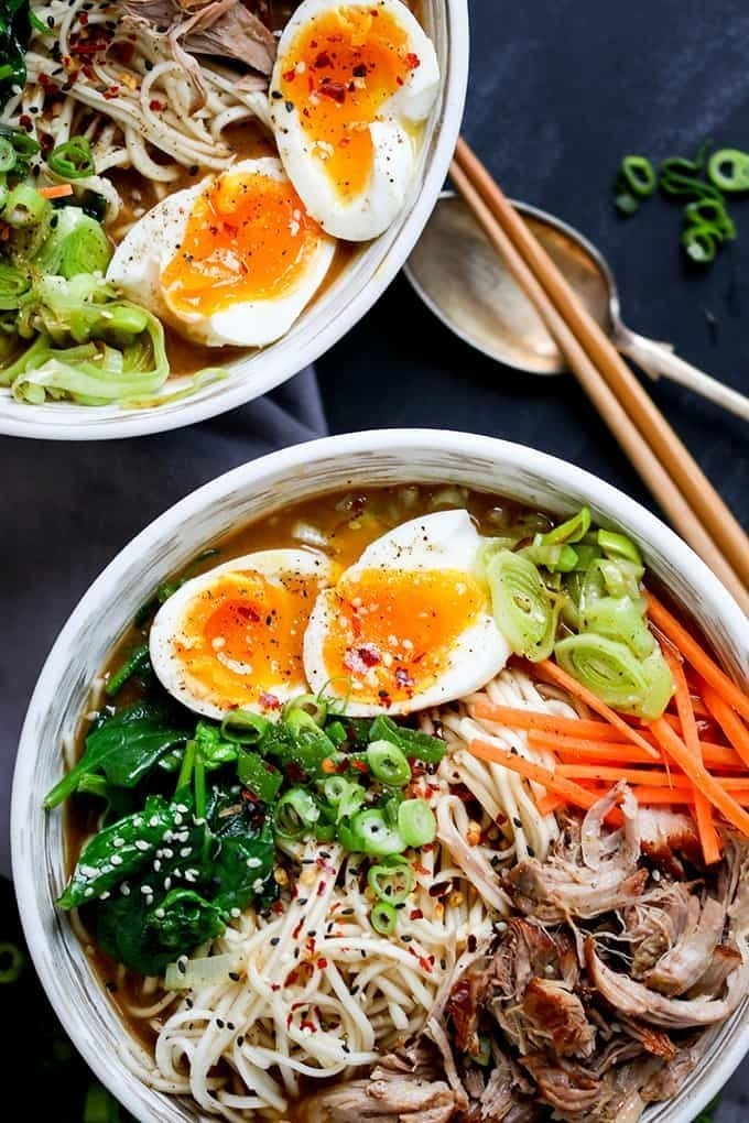 A bowl of ramen with shredded pork, spinach, carrots, scallions, and soft egg.