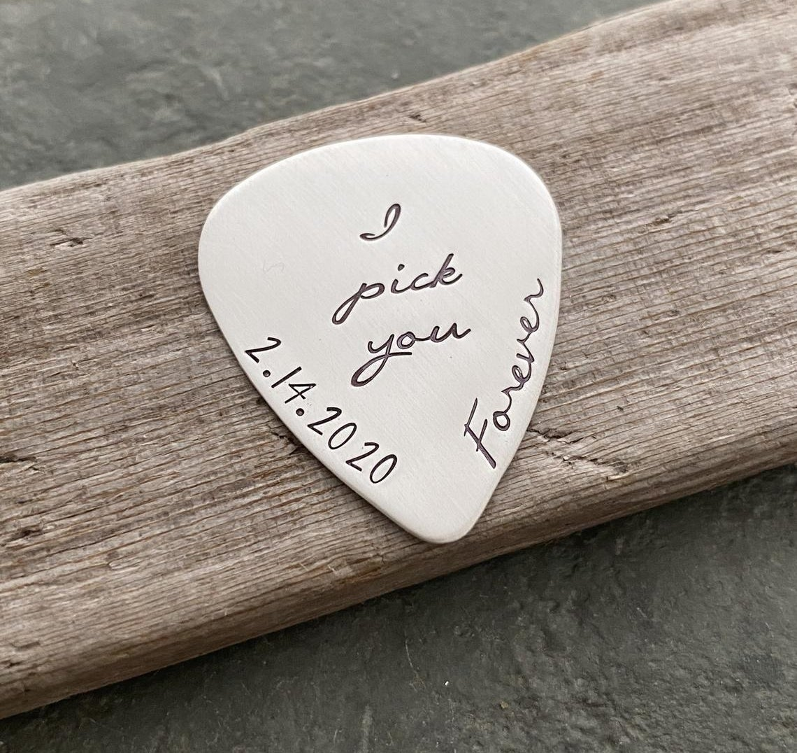 A silver pick with I pick you and 2-14-2020 forever engraved onto it