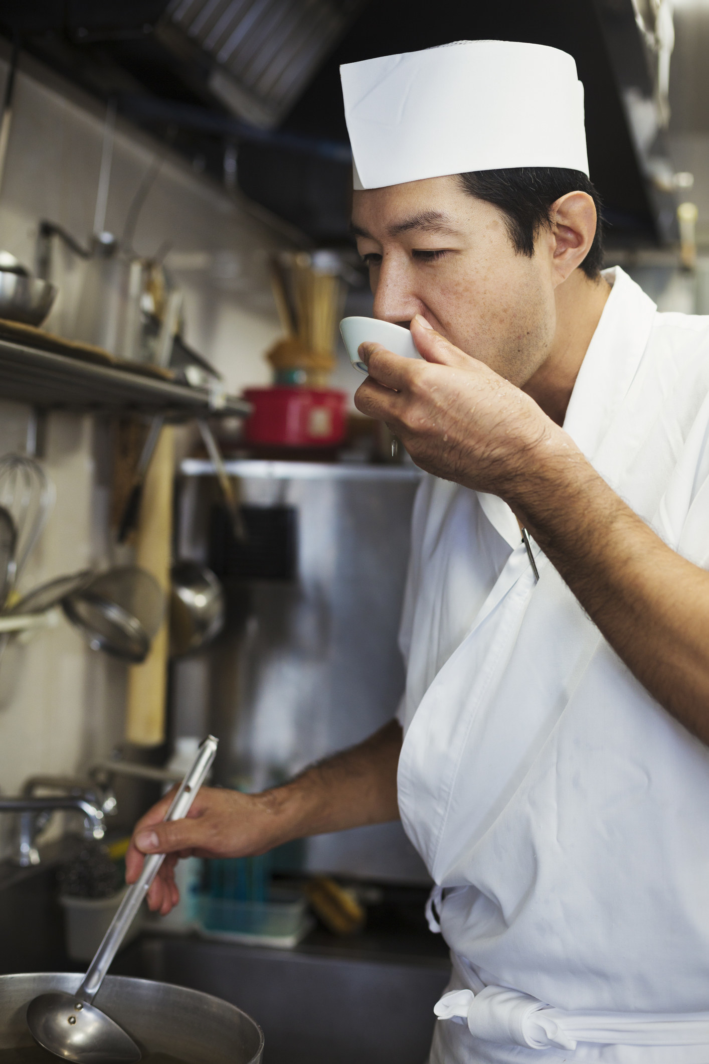 Chef working in the kitchen of a Japanese sushi restaurant, tasting food