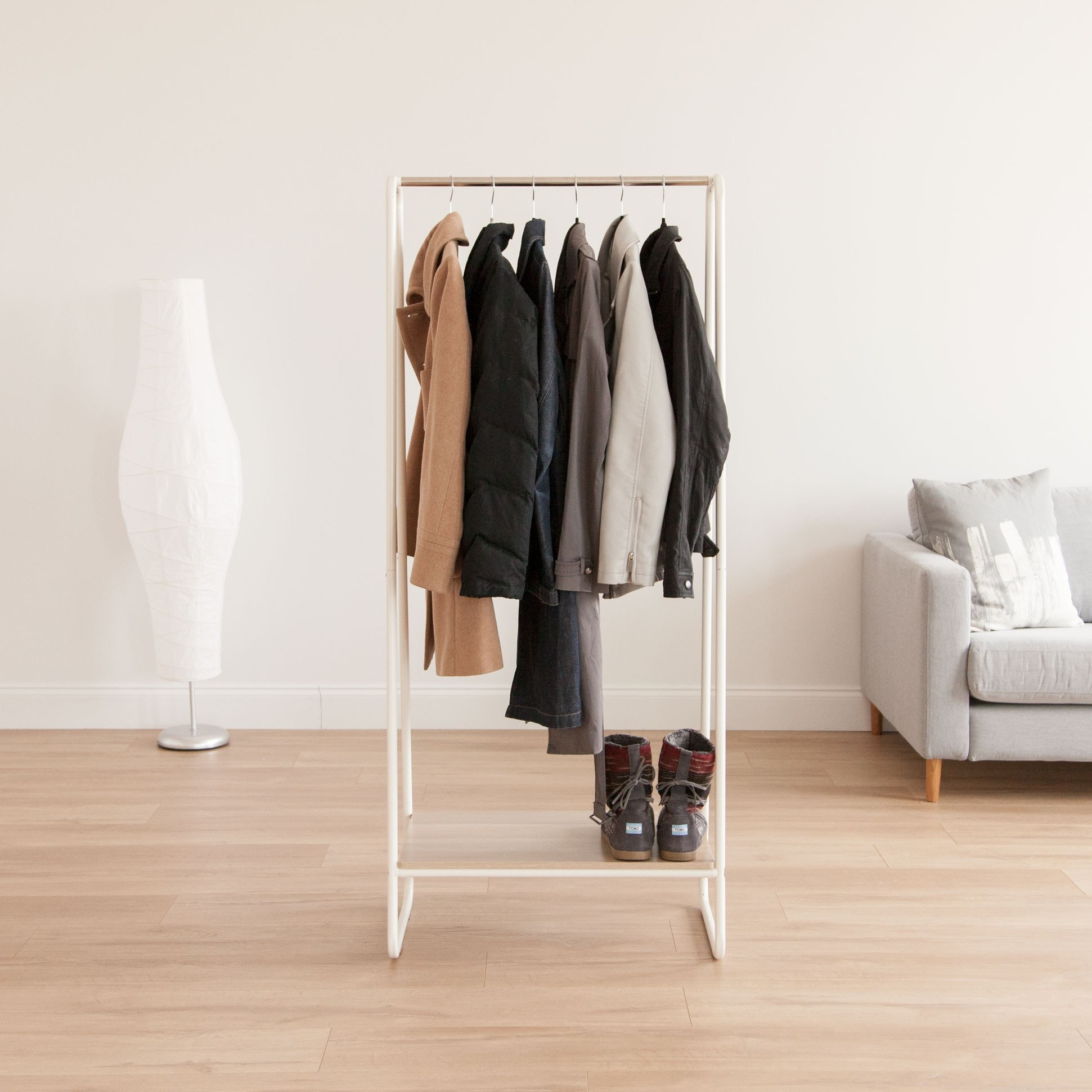 The garment rack in a room with several coats on it and a pair of shoes stored on the shelf underneath